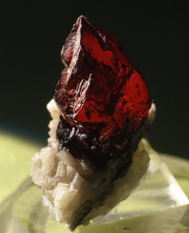 シナバー(Cinnaber) 辰砂(しんしゃ)・主成分:HgS(硫化水銀)・朱、バーミリオン(Vermillion)と言う名の方が一般的でしょう。朱色と言うと不透明なイメージがあるようですが、鉱物結晶自体はたいていその表面はうすい酸化二湯追って黒変していても光に透かして見ると美しい赤色をした透質の結晶です。最も古い赤色原料の一つで、天然の鉱物から粉体にして作った岩絵の具の辰砂などはとても高価です。写真の標本は高さが3cmほどある大きさの物です。標本産地:中国貴州銅仁鉱山