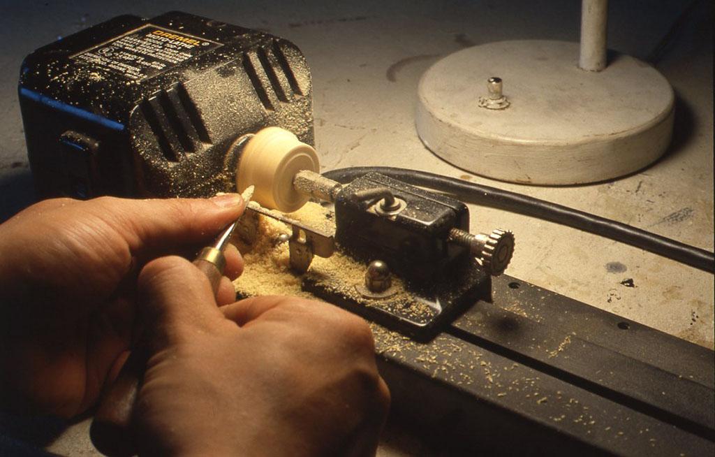 写真では小さなホビー用の旋盤を使っていますが、もちろんボール盤で作業できます。旋盤で作業できる場合はバイト(チゼル)という工具で削りますが、写真で見るように刃物を安定して使うための台(レスト)の部分がボール盤にはないので、木工のヤスリで作業をしたほうが安全です。