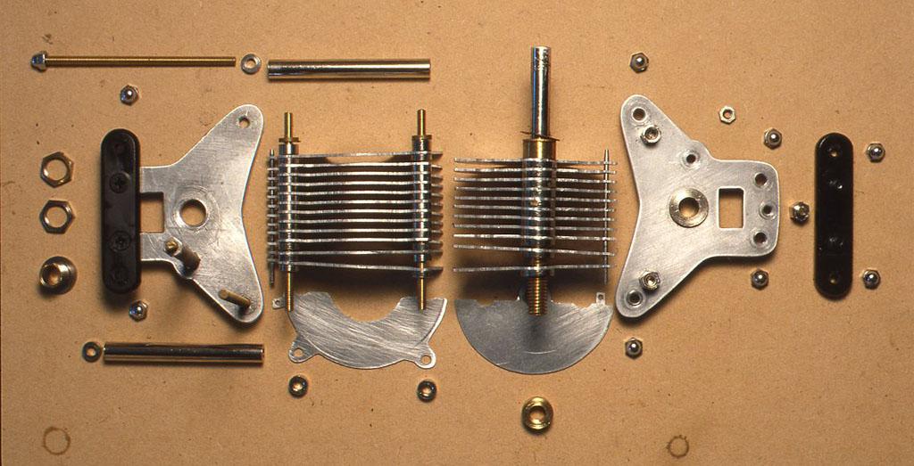 写真はAヴァリコンを分解したところです。ローター(回転するところ)が前面のパネルと導通しているので、パネルとステーター(羽の動かないところ)とを絶縁するために、黒いエボナイトの板があいだに入っています。