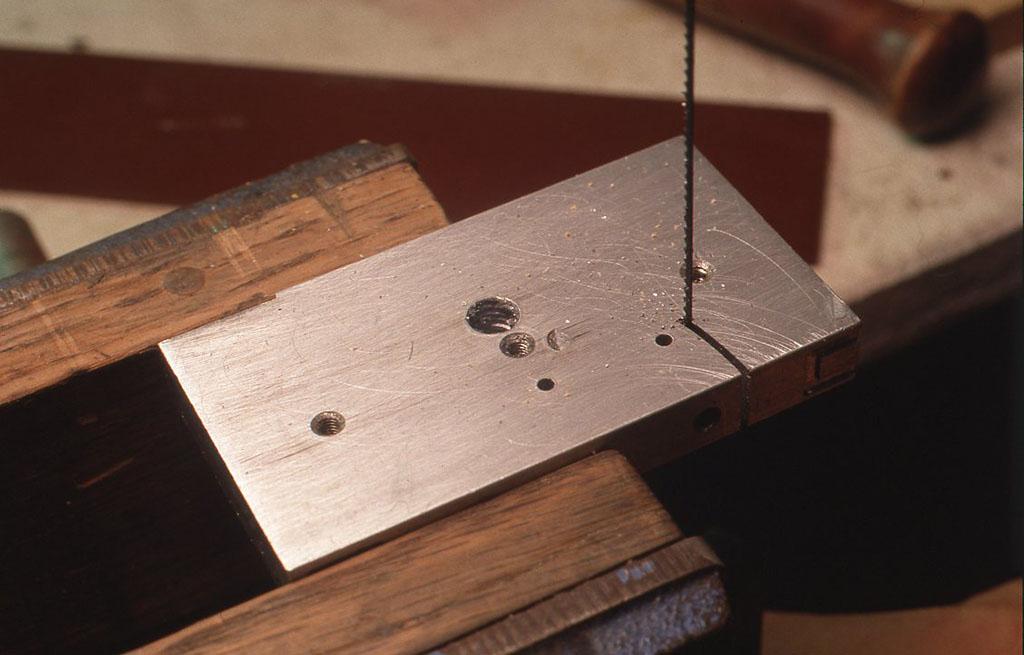 それぞれの羽を十分に取ることができるくらいの大きさにアルミ板を切り、貼り合わせたあと、糸ノコでカットする前にまず穴のほうを先にあけます。