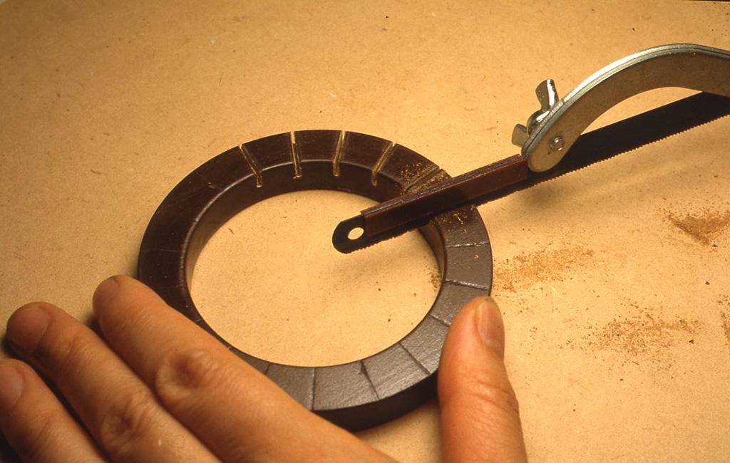 ニスを塗った木の輪に、 7mmくらいの深さの切り込みを19本入れます。切り込みの深さを一定にするためには、金ノコの背にあたる部分の両側にプラスチック片などを瞬間接着剤でとめて、ストッパーとしておくと仕事がやりやすいでしょう。