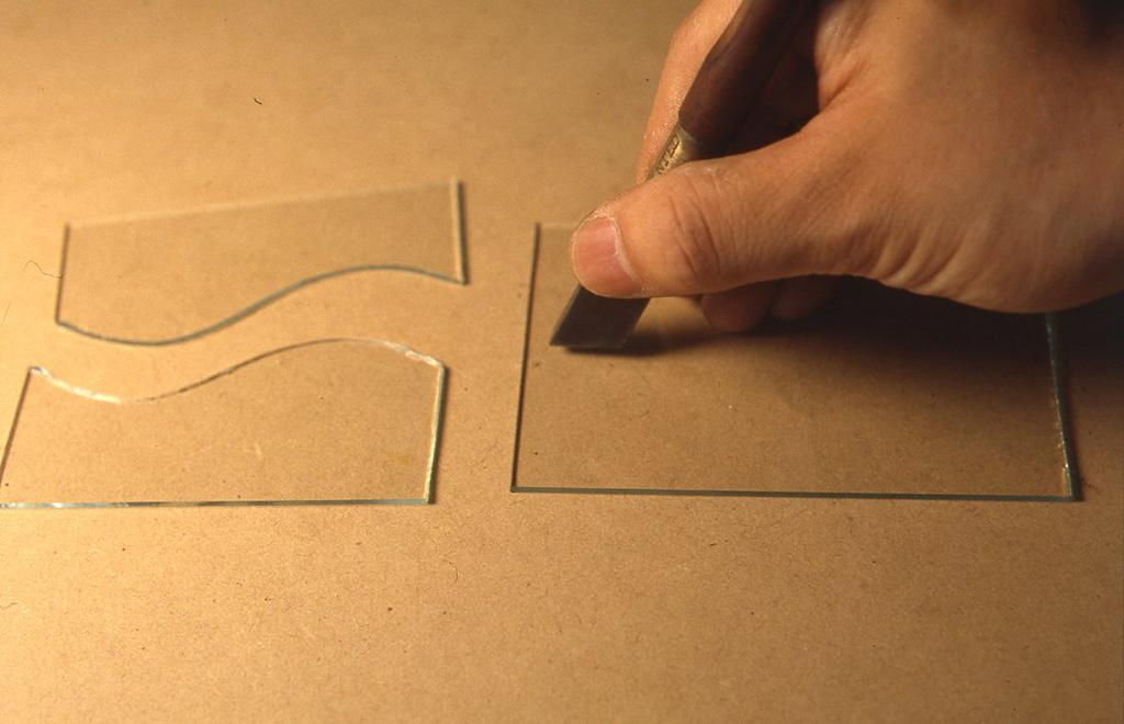 板ガラスを曲線でカットしている様子。フリーハンドでやっているが、直線にカットする場合は、まっすぐな木の棒などを定規にするといい。