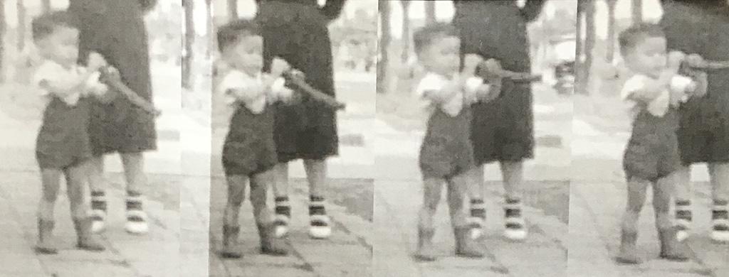 生まれた東京新橋界隈で、大好きなゴムホースで遊ぶ子供の頃の小林健二。