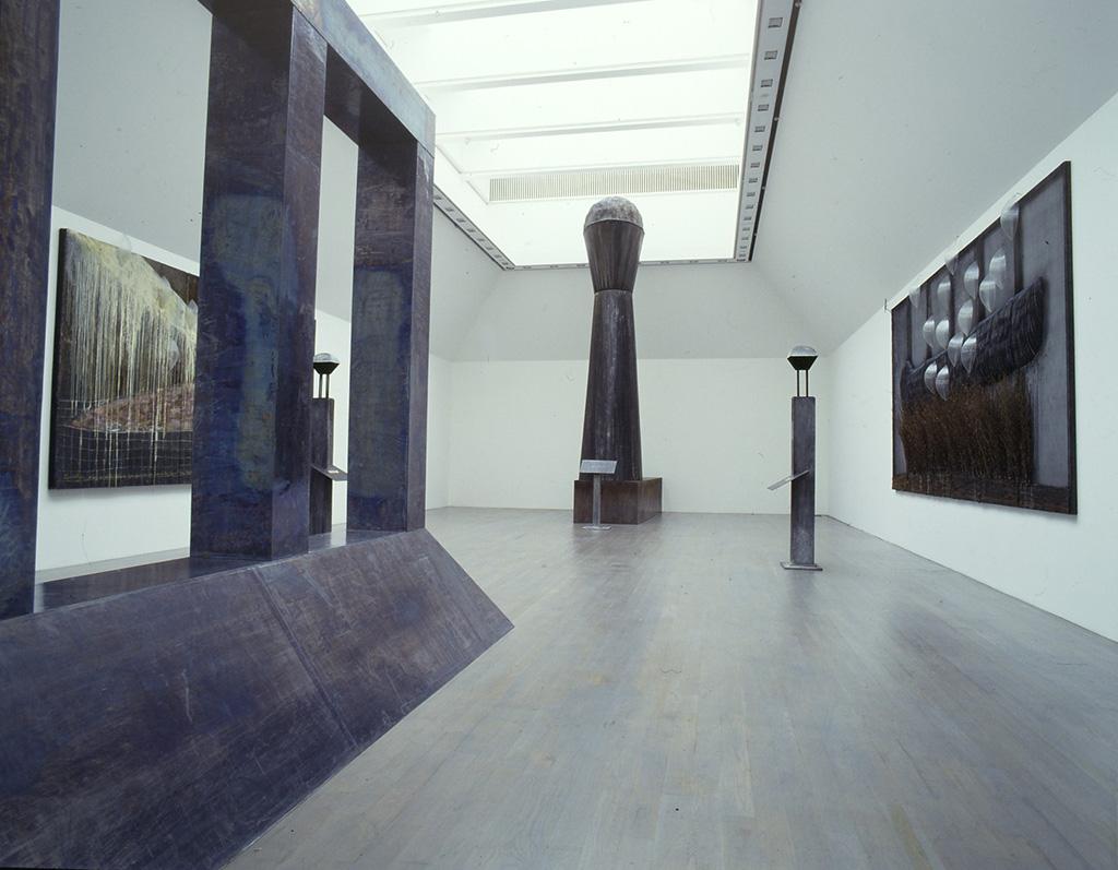 1991年の美術館での展示の一部。左の絵の重厚なパネル、中央の塔のようなもの、手前右の大きな立体は基本的に木工技術を中心に製作されている。塔のようなもので高さ7mもあり、このくらいの大きさになると、さすがに電動工具が活躍するそうだ。