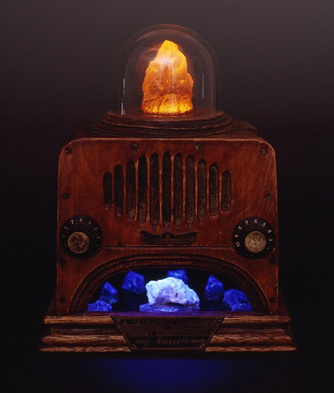 「PSYRADIOX(サイラジオ)」と名付けられた1987年の作品。アンティックラジオのように見えるが、筐体はもちろんプレートやツマミに至るまで自作されている。木工技術を使った作品の中でも小さなものではあるが、小林氏は趣味的にもこのような工作は好きであると言う。ちなみにこのラジオは受信した放送の音量によってガラスドーム内の結晶が光りながら明滅氏、また色の七色に変化する。