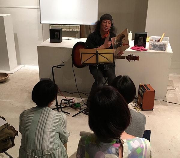 小林健二ミニライブが始まる前に、高校時代に絵を手にって説明している小林健二。