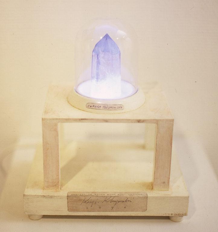 「CRYSTAL OF AZOTH WITH AURA TRIGGER 」          木、結晶、電子回路など        wood,crystal,electric circuit,others 240x200X150 1992-1994  [CRYSTAL OF AZOTH(霊の鉱石)]とは本来セファイドの水の結晶です。その結晶の左側に陽性起電微子を、その右側に陰性消失微子を発生着帯します。アレフ(空あるいは風)、メム(水あるいは海)、シン(火あるいは熱)のそれおぞれ緑、青、赤の色彩成分をアゾト(霊あるいは意識)によって封じられた結晶なのです。この結晶はアルプス地方に産する明るい煙水晶で、その中に極めてわずかに見つけられる古代セファイドの水を含有したものを使用します。その左側に手をかざすと陽性起電微子ーAZOTHIN(アゾシン)の一種によって発光する場ができ、右側においてはその反対の作用が起ります (左の柱に手をかざすと水晶内部にゆっくりと光が現れはじめ静かに色彩が変化する。右の柱に手をかざすとまたゆっくりと消える)