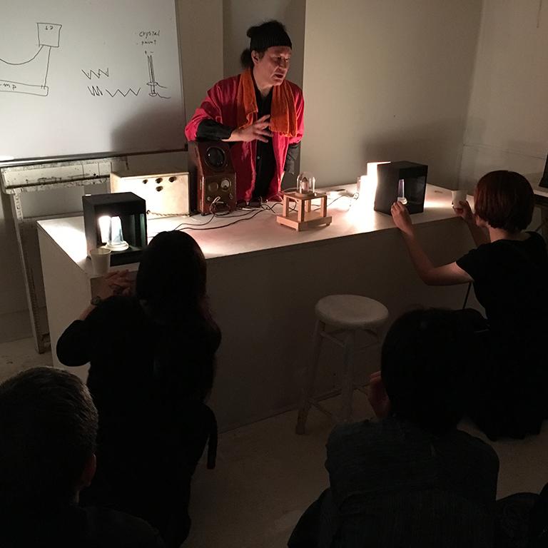 [遠方結晶交信機] 別の場所にいる人々交信し合える装置。水晶のような結晶の表面にのみ、お互いの動画が映し出される作品。一つのトーク会場で紹介するため、今回は2mほど離れたいるが同じテーブルの上で実験。