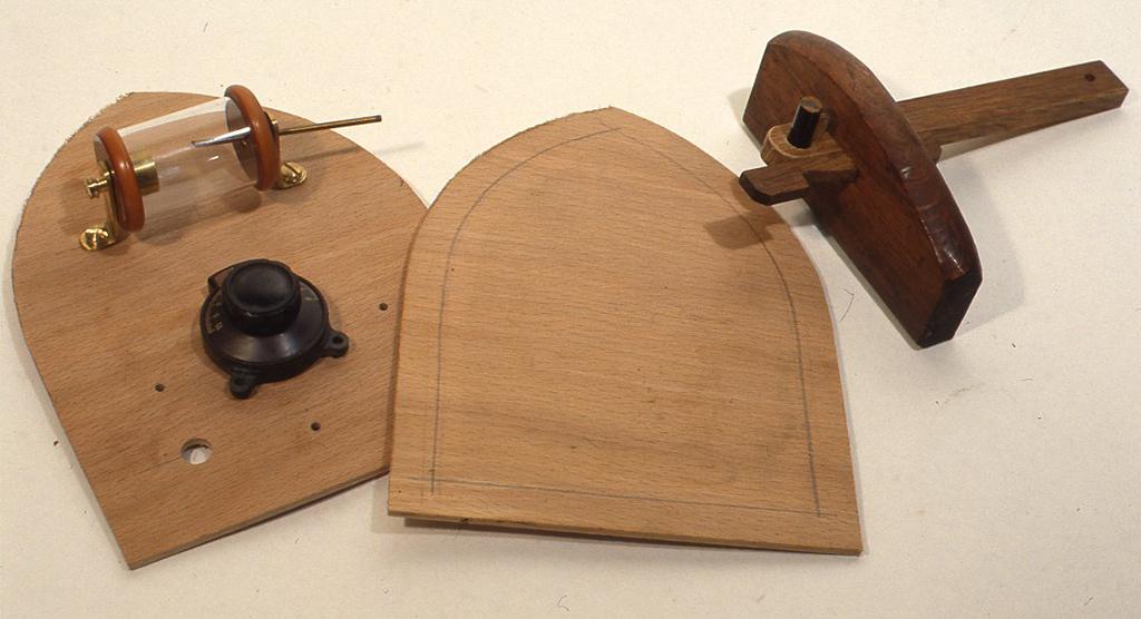 正面のパネルを作ります(写真15)。パネルのレイアウトをよく確かめて補強と装飾を兼ねてパネルの縁を二重にします。まずパネルと同寸の板をもう一枚切って、縁から一定の幅(作例では12mm)にケヒキなどでしるしをつけて、弓ノコなどで切り抜きます(写真16)。