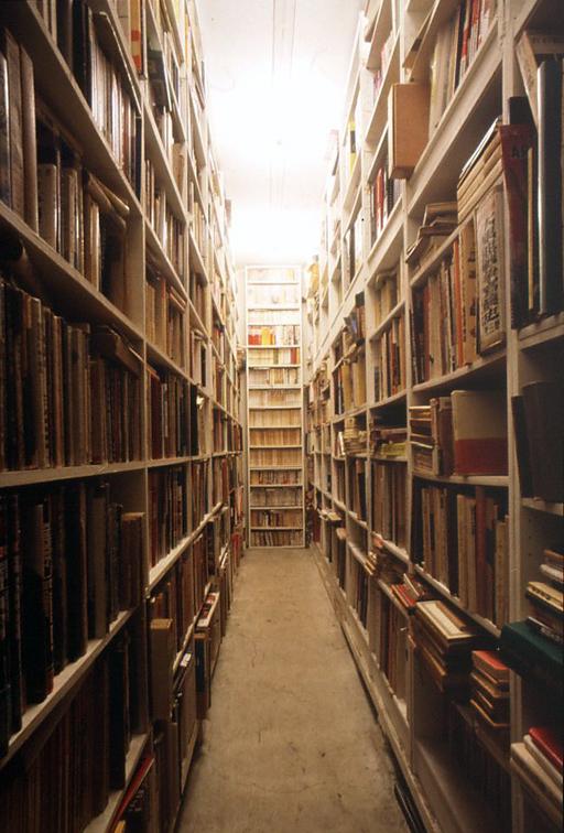 1999年頃の小林健二アトリエ(車庫を改造して作った書庫。天井まで続く書棚には古今東西から集められた書籍の数々。)
