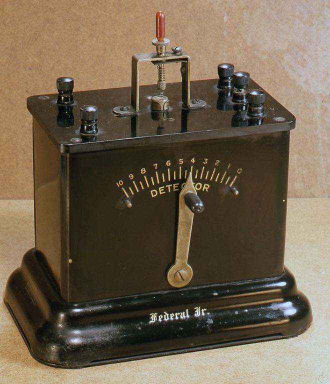 これは米国フェデラル社製で、フェデラルジュニアと呼ばれるものです。ボディは金属製で表と裏にそれぞれアンテナとディテクターをコイルヘ接合する可変ノブがついています。1910年頃のものです。H235× W215× D145(mm)