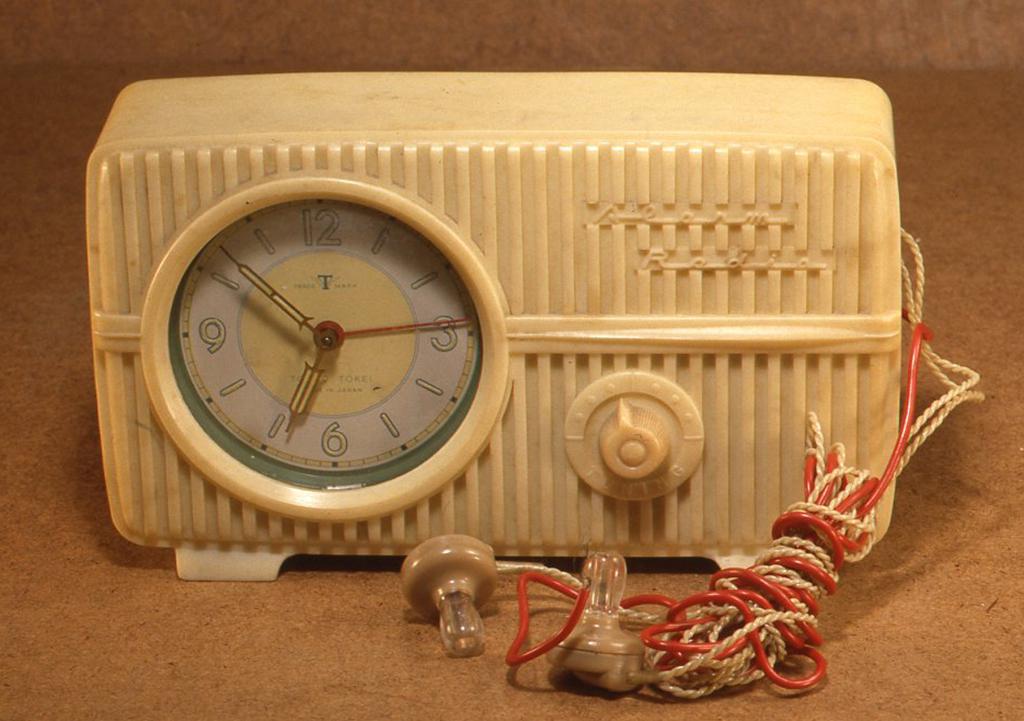 これは昭和30年代のゲルマラジオの付いた時計で、東京時計社製です。クリーム色のベークライトのボディで、クリスタルイヤフォンが2つついていて2人で放送を聞けるようになっています。H113× W193 X D54(mm)