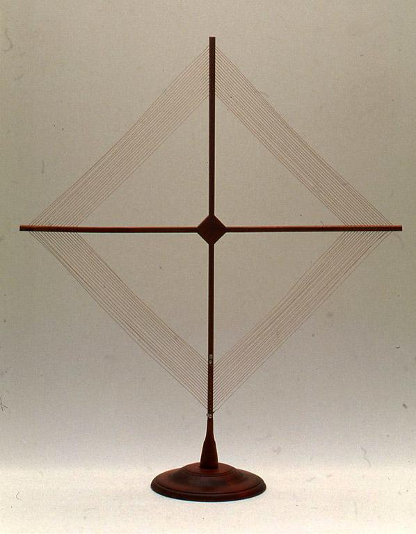鉱石ラジオが使われていた時代の室内アンテナは写真のようなタイプのものが多く、主に真空管式の受信機に使われていました。この自作した室内アンテナは高さは約72 cmで腕の長さが1本30 cm、張ったワイヤーが約23mと小さなものです。作例では0.08/30の絹巻リッツ線というものを使用しましたが、0.6mmくらいのエナメル線でも同じです。 あまり大きくなると感度はよくなっても置き場所に困ると思ったからですが、これでもそれなりにアンテナとして働いてくれます。ほんとうはもっと巻き数を増やしてワイヤーの長さをかせいだ方がよいでしょう。