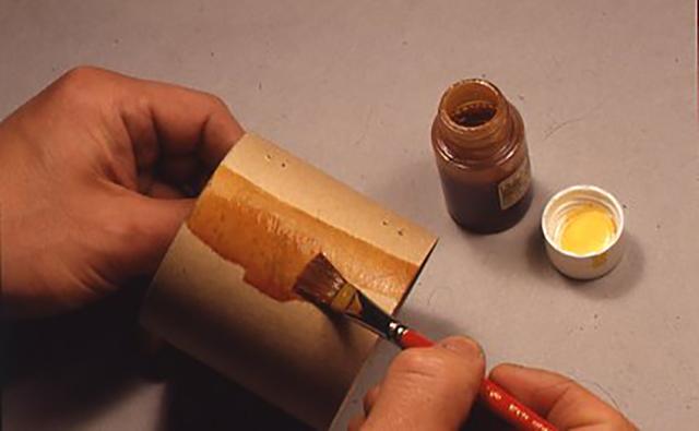 ニスを巻き筒に塗っているところ。このようにすることでベークライト製の筒のような感じにもなり、強度が出る。薄く何回もウラオモテを乾かしては塗るようにする。 キットに筆は付属していない。乾かす間、筆はラップで包んでおき、洗浄には燃料用アルコールを使う。