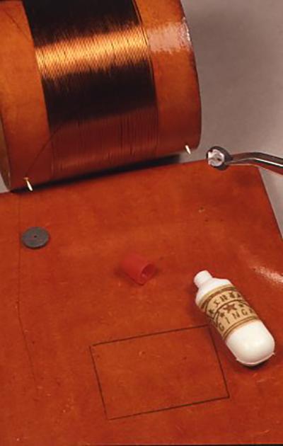 コイルを板に取り付ける位置に付属の接着剤でスペーサーの厚紙を貼る。