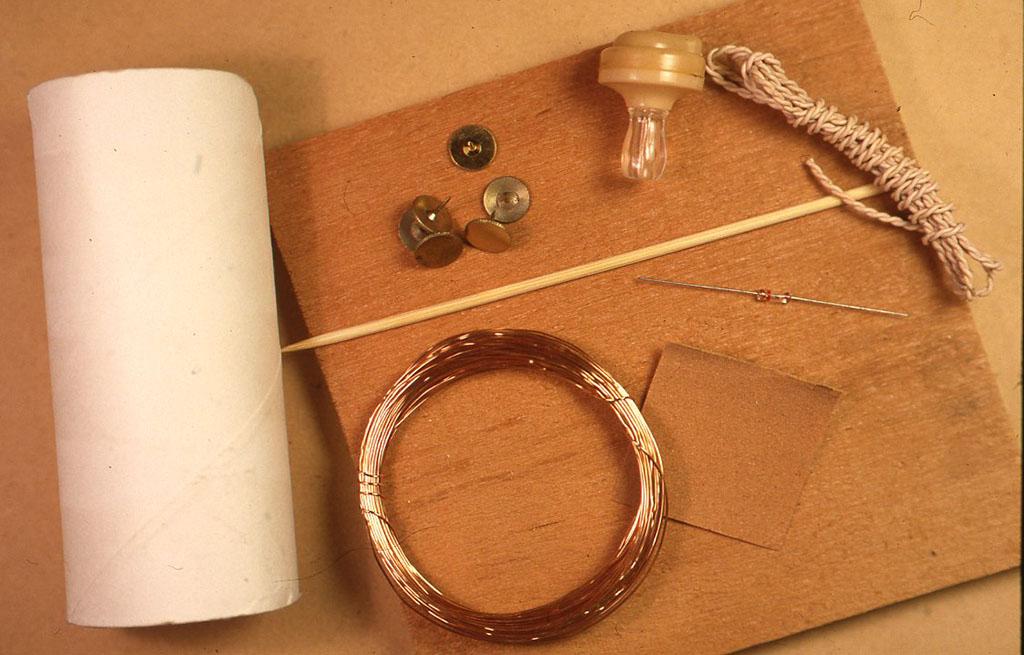 材料・ トイレットペーパーの芯 1本/ 15 cm角くらいの木の板 1枚/ 竹串 1本/ 画鋲 5つ/ エナメル線 20mほど/ クリスタルイヤフォン 1個/ グルマニウムダイオード 1本(使用する時、向きはどちらでもよい)/ サンドペーパー少々