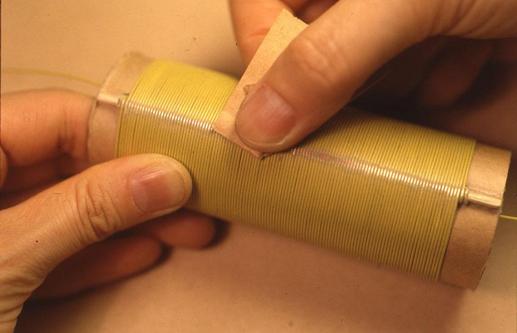 巻き数は120~ 150回くらいです。ひととおり巻きおわったら巻きはじめと同じようにして固定し、引き出し線を10~ 15 cmくらい残して切ります。 竹串によって出っ張った部分の被覆をサンドペーパーではがし、銅を露出させます。(作例では、見やすいように色のついた線を使用しています)