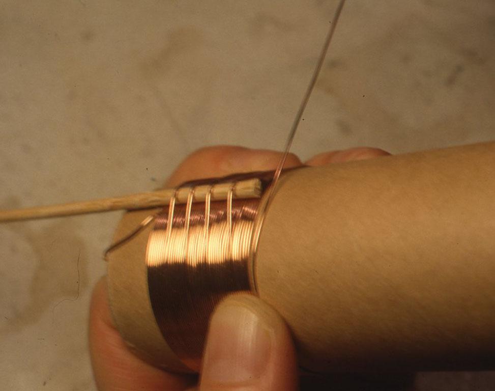 まずトイレットペーパーの芯に2つ穴をあけてそこにエナメル線を通し、10 cmくらい引き出して巻きはじめを固定します。10回巻いたところで竹申を横から入れて、 1回竹申をまたがせて巻き、また竹申をはずして10回巻きます。10回目、20回目、30回目と竹串をまたがせて巻くことでタップを出していきます