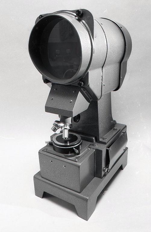 投影型偏光顕微鏡 このような小型(投影型では)のものを最近あまり見なくなった。今回のようなギャラリーでの展示に使用するのには上部の投影板(像が映る曇りガラスの部分)は暗く、照明用の ハロゲンランプの発熱の為必要な、強制冷却ファンの音が大きく、必ずしも理想的ではないかもしれない。個人的観察の為に入手したもので、比較的安価出会ったのと、何よりこの奇妙な形体に引かれたところがあった。