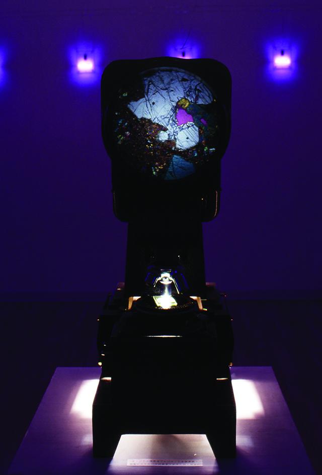小林健二個展[EXPERMENT1] 小林自作のプレパラートがピンク色のバックライトとともに会場に展示され、多重焦点式の自作プレパラートを中央の偏光顕微鏡にて観察できる。