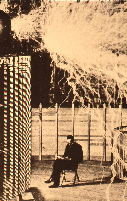 自身が発明した装置の前で本を読むニコラ・テスラ(Nikola TESLA)
