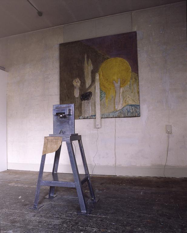 「私たちは自分たちの故郷を鉛色に変えつつありながらも理想郷をいつも夢見ている。」 木、鉛、鉄、紙、電子部品、キャンバスに油彩(電磁石を使った特殊な仕掛けにより前にある作品の球が浮いている) 2300X1300X2000mm  1989