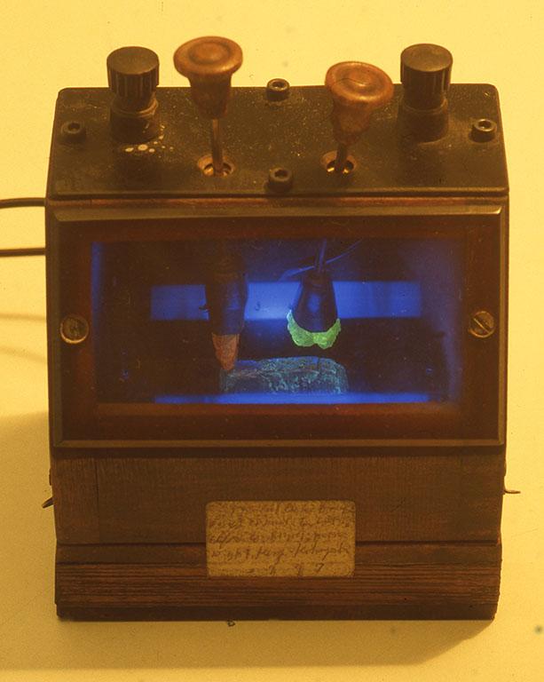 小林健二作品[夜光結晶短波受信機] ディテクター(検波部)、中の発光し透き通る赤色と緑色の石を、青色に光っている金属に当てるとヅピーカーから音が聴こえる。