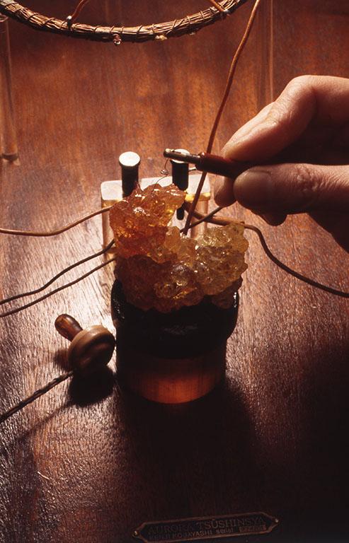 小林健二作品[IN TUNE WITH THE PAST TENSE] 透きとおった鉱物にタングステンの針を当てて検波すると、クリスタルイヤフォンで放送を聴くことができる。