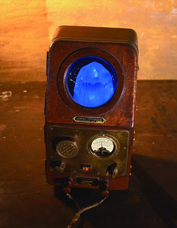 [BLUE QUARTZ COMMUNICATOR(青色水晶交信機)] 内部に閃ウラン鉱(ウラニナイト)が組み込まれており、そこからでる放射線(人体には無害な微量)をガイガーミューラー菅で検知し、それを特殊なフィルターがモールス信号のように変換している。筐体には入りきらないほど大きいはずの水晶がゆっくり回転し、その音とシンクロして白く明滅する作品。
